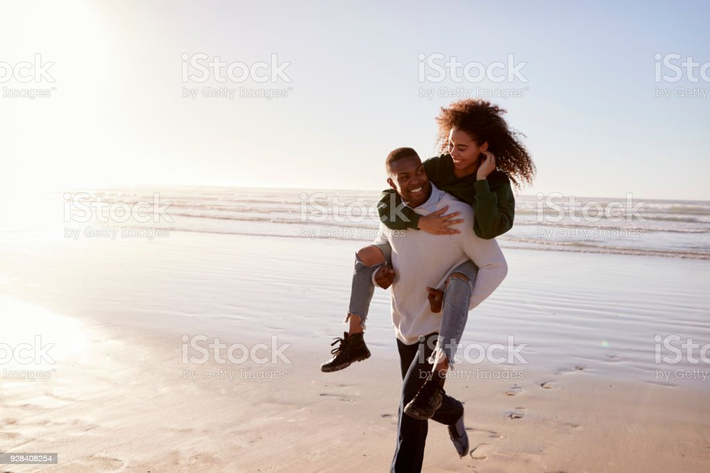 Man Giving Woman Piggyback On Winter Beach Vacation stock photo