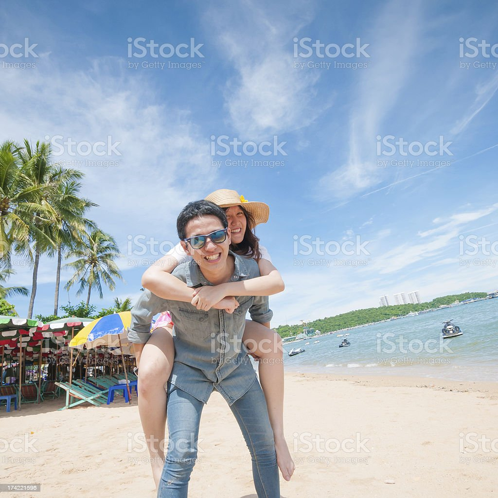 Man Giving Woman Piggyback Ride At The Beach Stock Photo