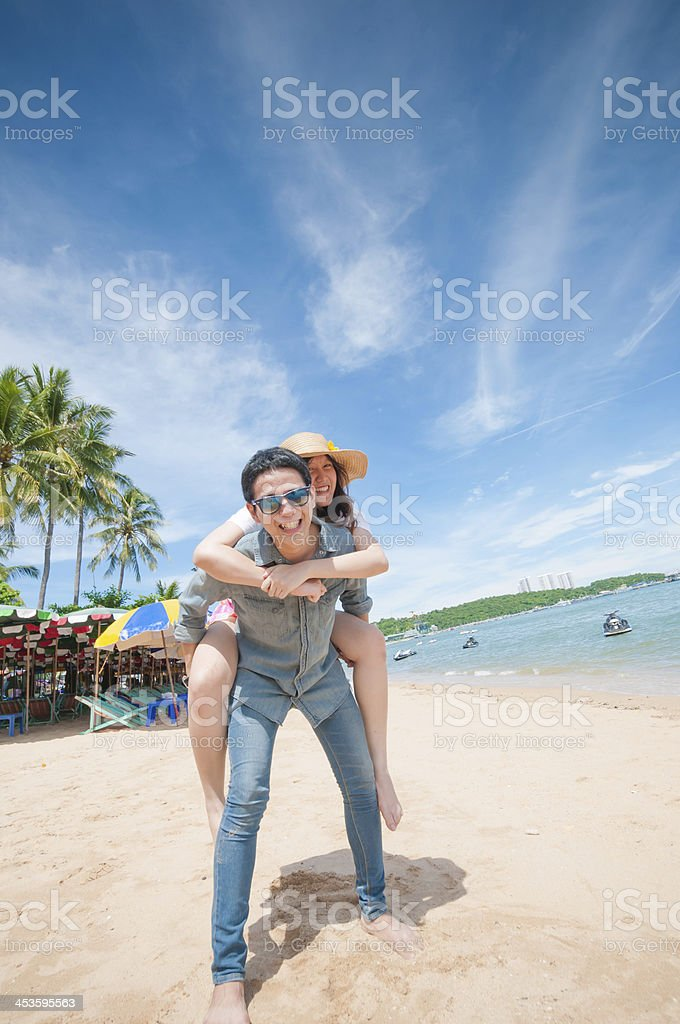 Man giving woman piggyback ride at the beach. royalty-free stock photo