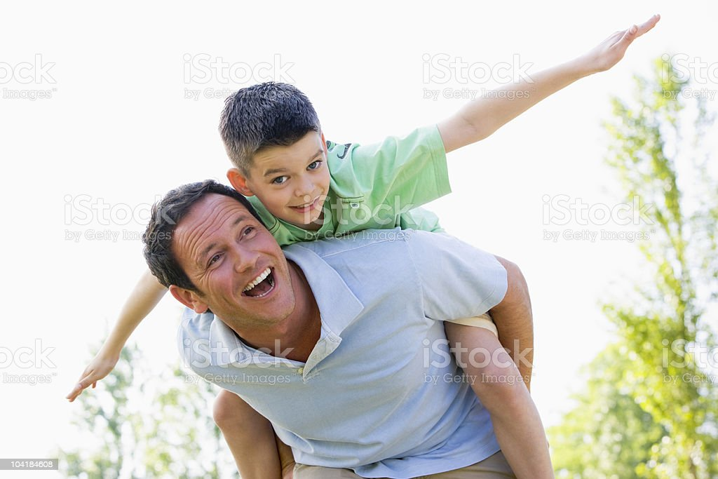 Man giving young boy piggyback ride outdoors stock photo