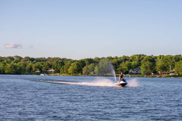 Man goes jet skiing on Lake Bowen in upstate S.C. Inman, S.C. / USA - May 5, 2019: A man enjoys jet skiing on Lake Bowen, a man-made reservoir, on a summer day. spartanburg stock pictures, royalty-free photos & images