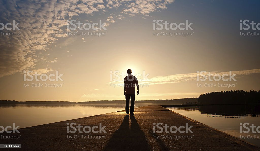 Man goes on concrete pier in the sunrise royalty-free stock photo