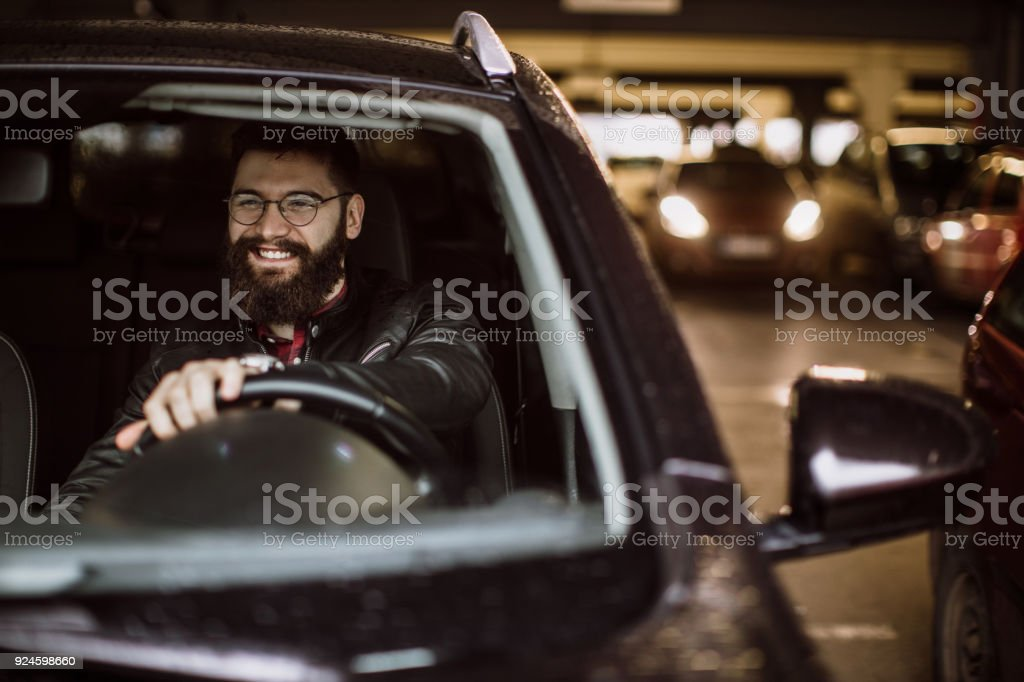 Man goes out of the parking lot stock photo