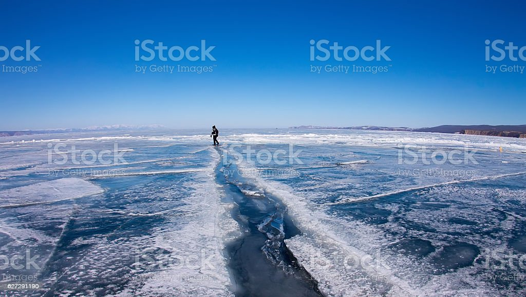 Man goes through large crack in ice of Lake Baikal stock photo