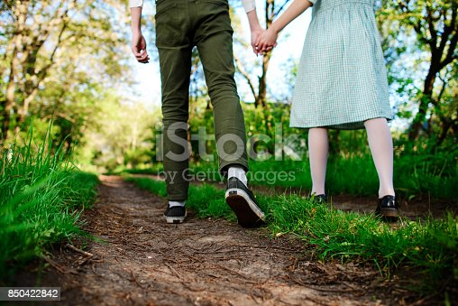 man goes with his girlfriend on the road, low angle, Back view.