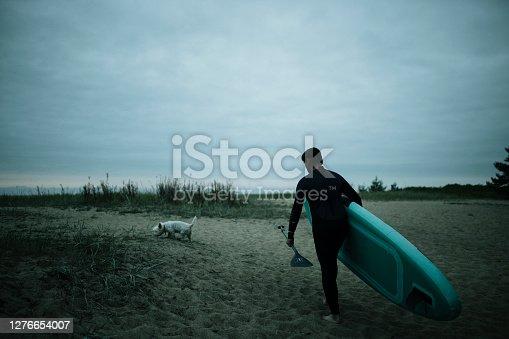istock Man going paddleboarding at dusk 1276654007