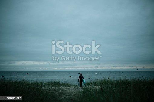 istock Man going paddleboarding at dusk 1276654017