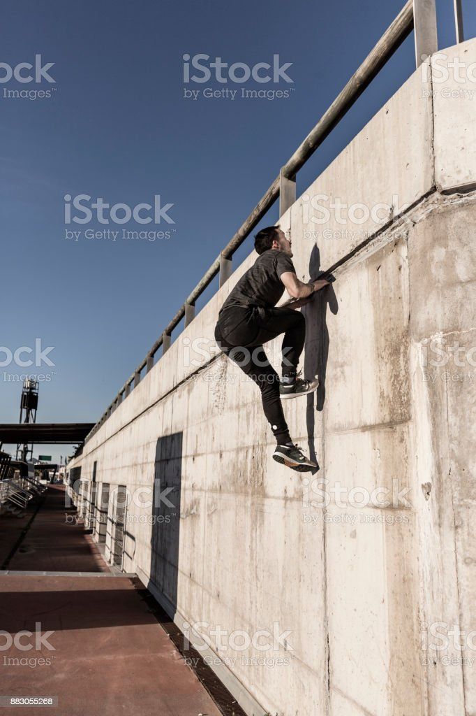 Man going up wall practicing parkour in the city stock photo