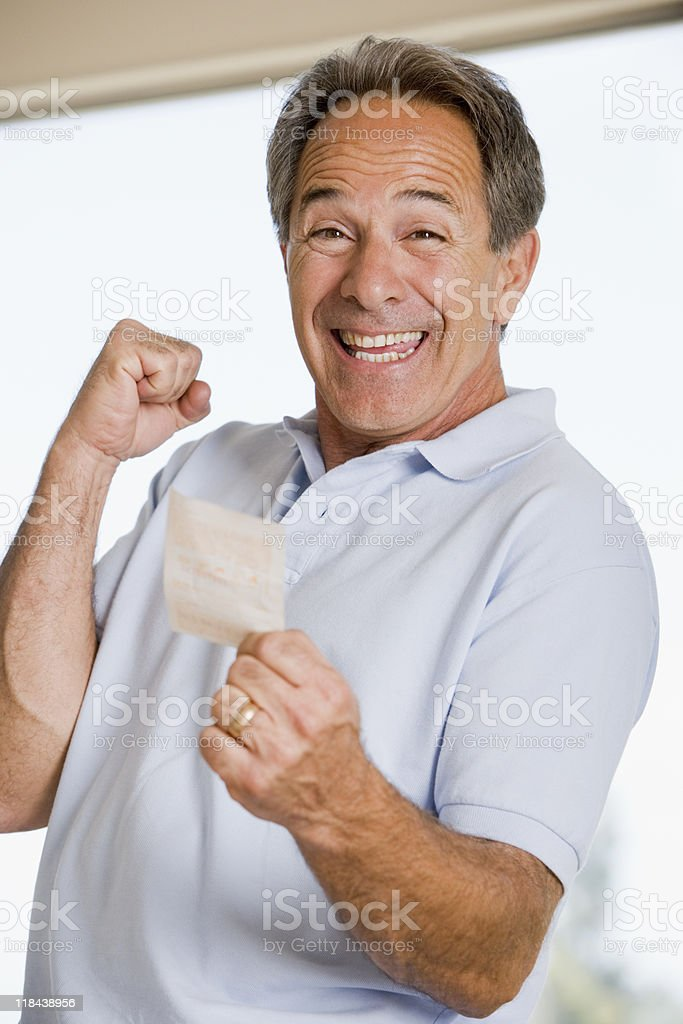 Man going yes with winning lottery ticket stock photo