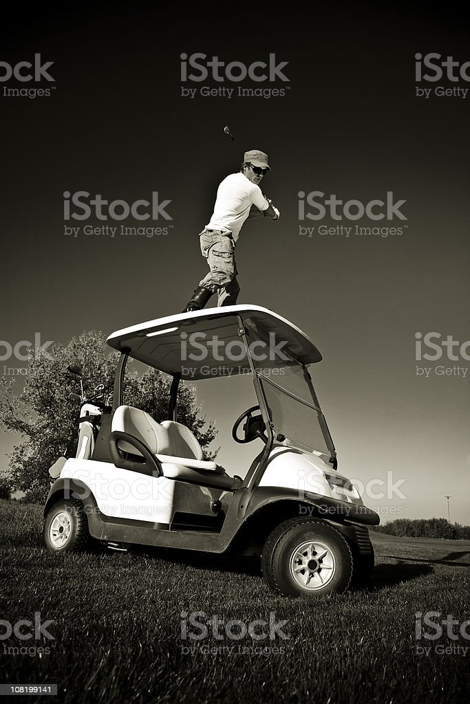 Man Golfing off Roof of Golf Cart,  Black and White royalty-free stock photo