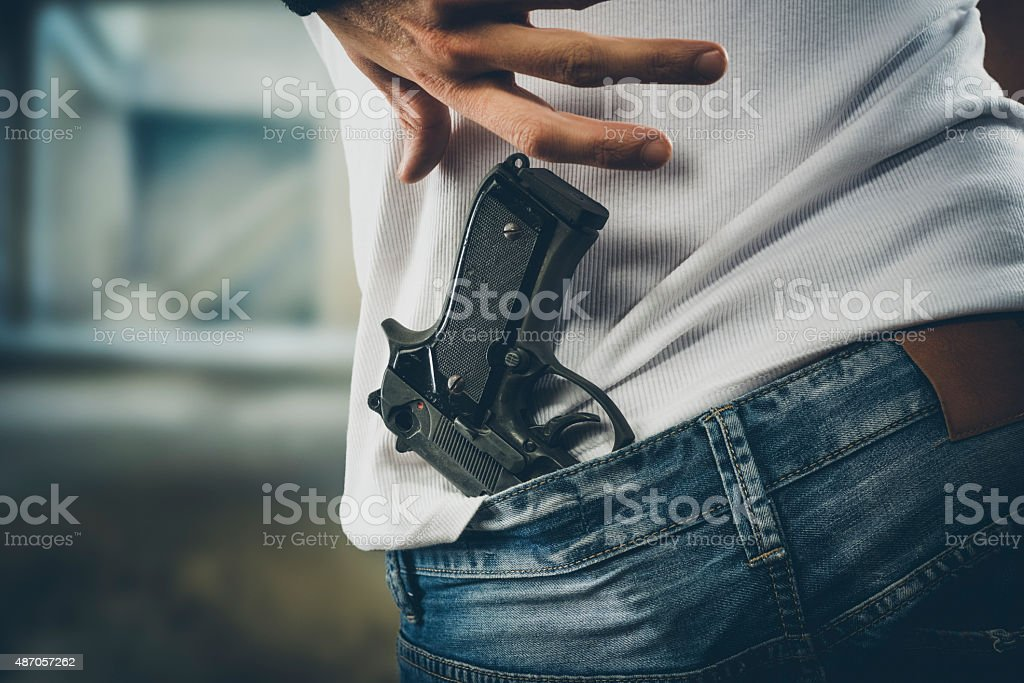 Man grabbing his pistol stock photo