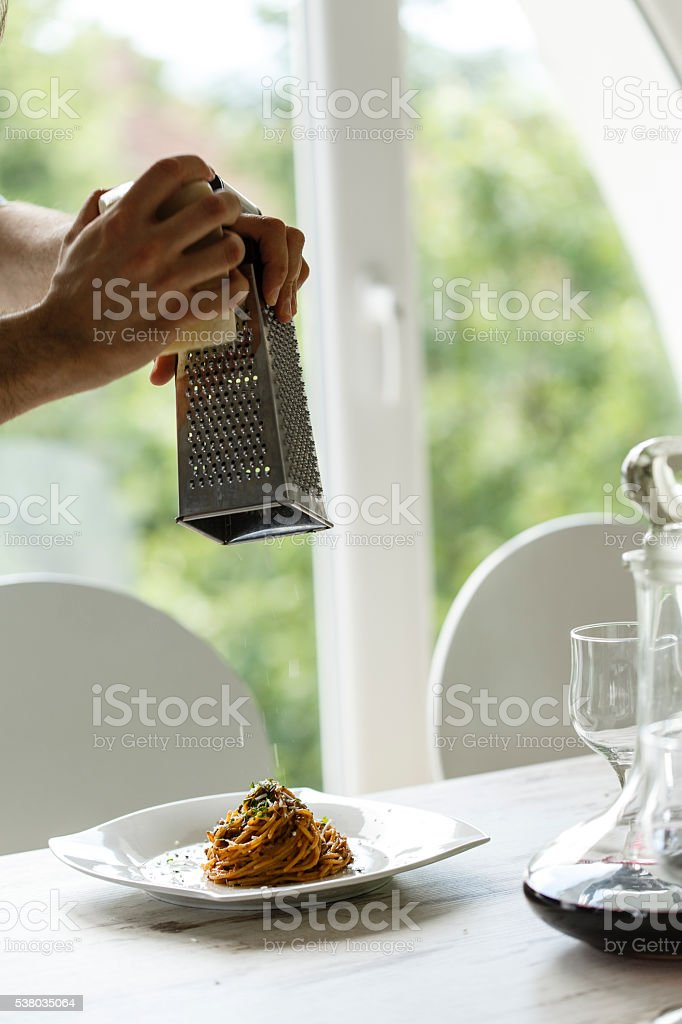 Man grating cheese over spaghetti stock photo