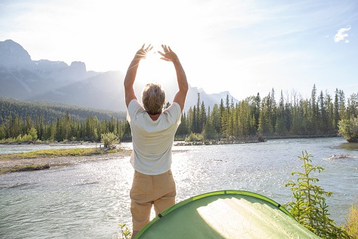 Man greets the rising sun outside of his tent on a river