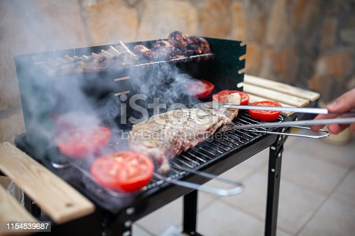 Man grilling meat chops on barbecue