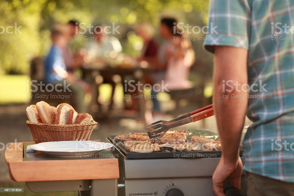 Man grilling meat on barbecue grill stock photo