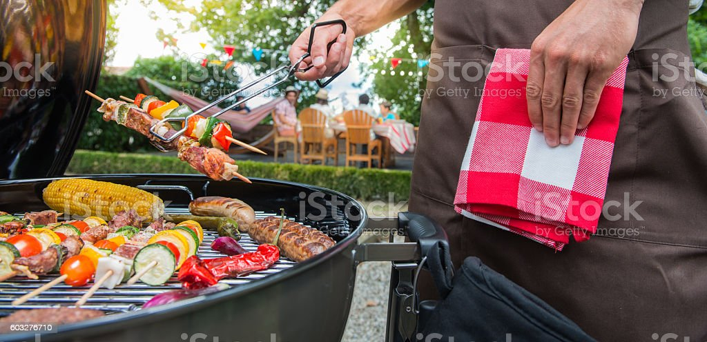 Man grilling meat on garden barbecue party stock photo