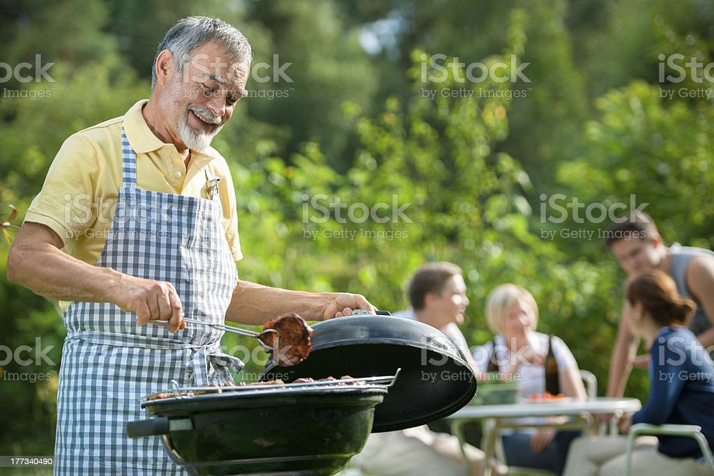 Man grilling on barbecue with friends in background royalty-free stock photo
