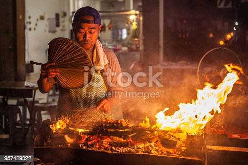 A man grilling satay, a favourite local dish or street food of skewered meat of beef and chicken. His stall is located by the roadside, and tables and chairs are prepared for diners. Such satay stalls can be found all around cities like Kuala Lumpur and around Malaysia.