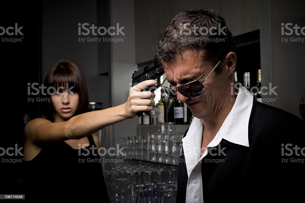 Man Grimacing While Woman Holds Gun to His Head royalty-free stock photo