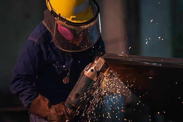 Hombre usando la trituración en taller casco duro y guantes. - foto de stock