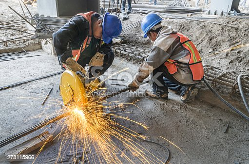 istock Man grinding metal tubes with protective equipment 1278115966