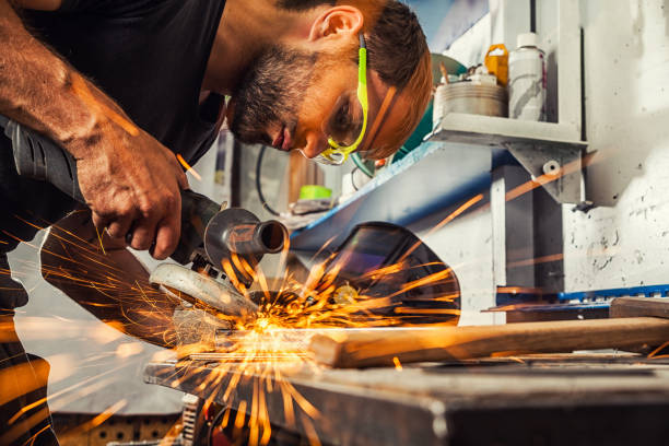 man grinding metal with a angle grinder A young man welder a brunette in a black T-shirt and safety goggles. He processes a metal item from a angle grinder in the workshop. Close-up on the sides fly sparks from the  a angle grinder metal worker stock pictures, royalty-free photos & images
