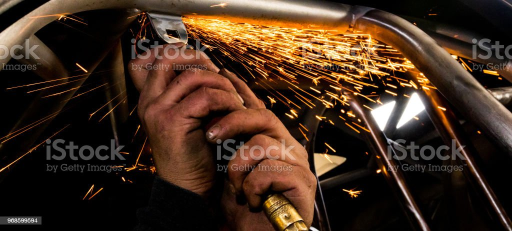 Man grinding steel tubing with a hot pneumatic grinding disc showering sparks and slag stock photo
