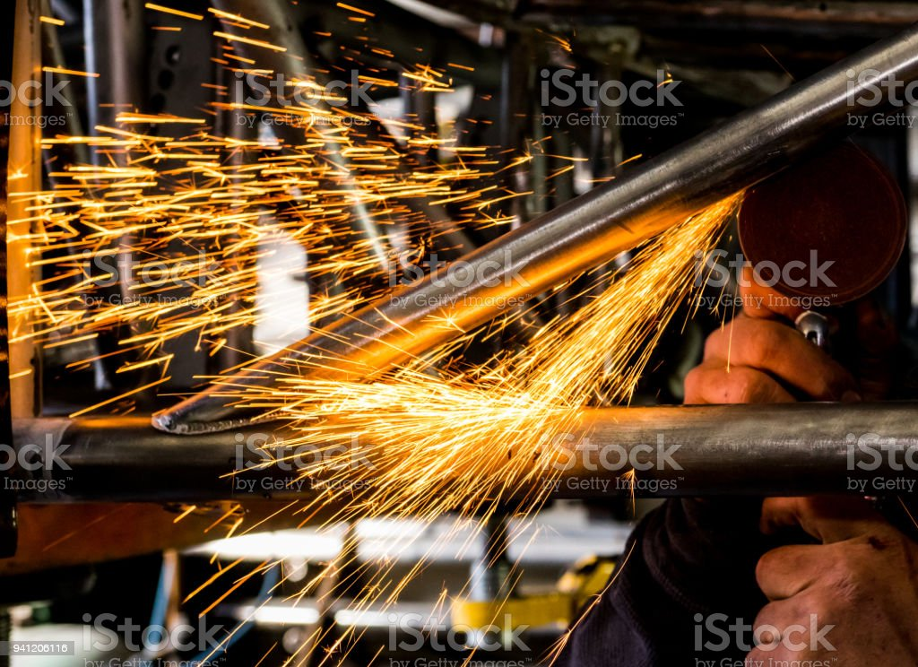 Man grinding steel tubing with pneumatic grinding disc showering hot sparks and slag stock photo