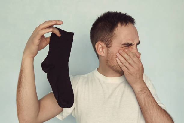 man grips nose with fingers holding a smelly sock in hand stock photo