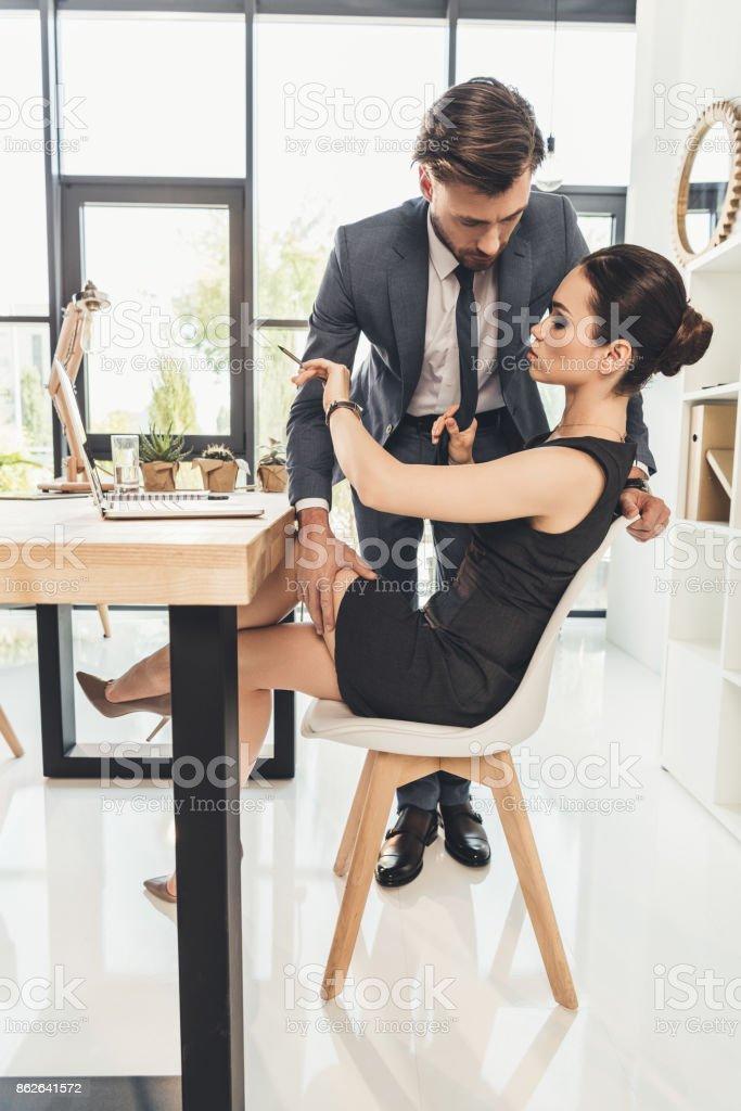 man groping secretery on thigh stock photo