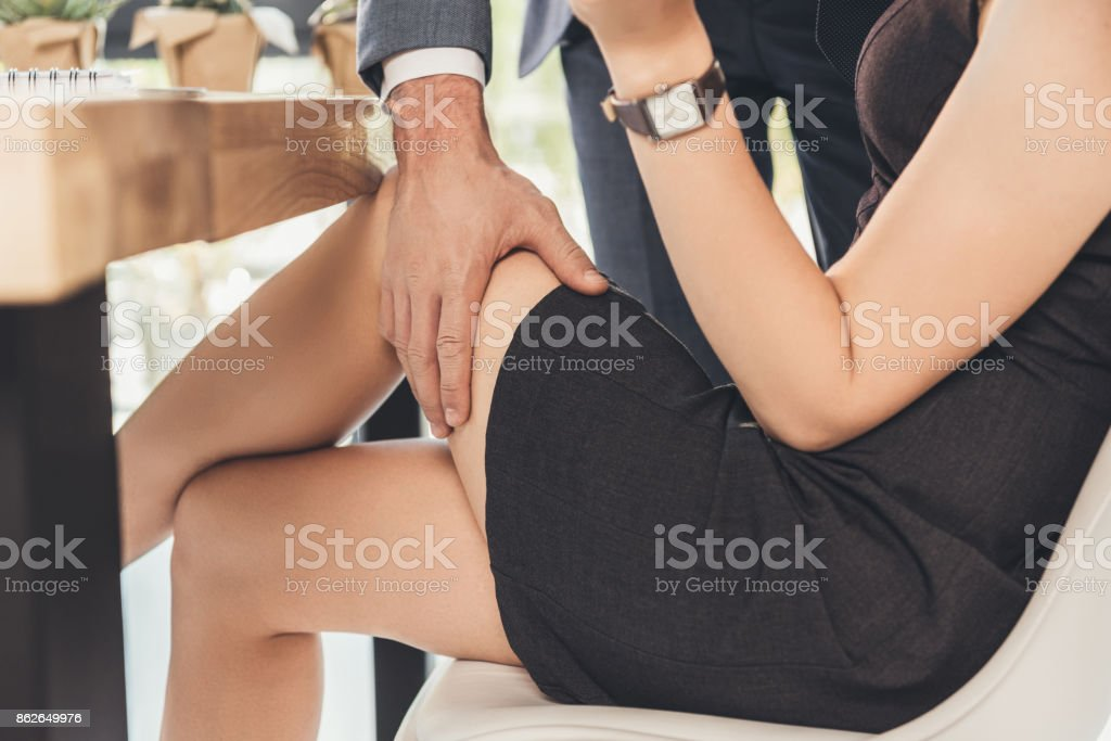 man groping woman on thigh stock photo