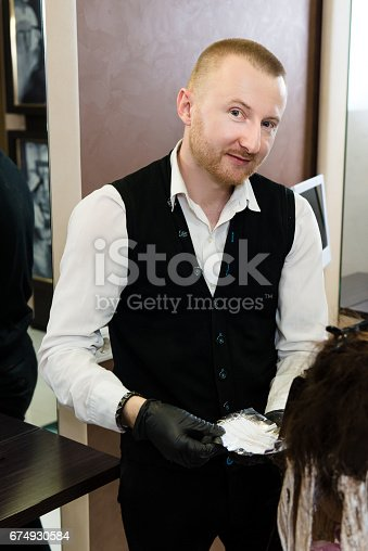 istock man hairstylist posing for a picture while working with his client's hair 674930584