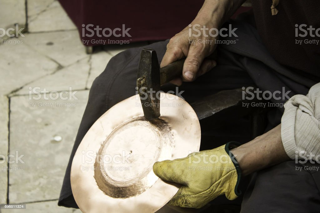 Man hammering tinplate stock photo