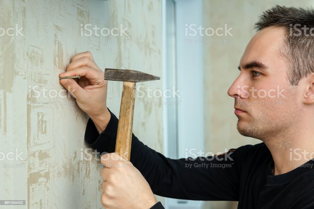 A man hammers a nail into plaster wall under the Wallpaper stock photo