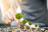 istock Man Han putting coins stacking with glowing of tree. Growth business saving and investment concept. 1179161401