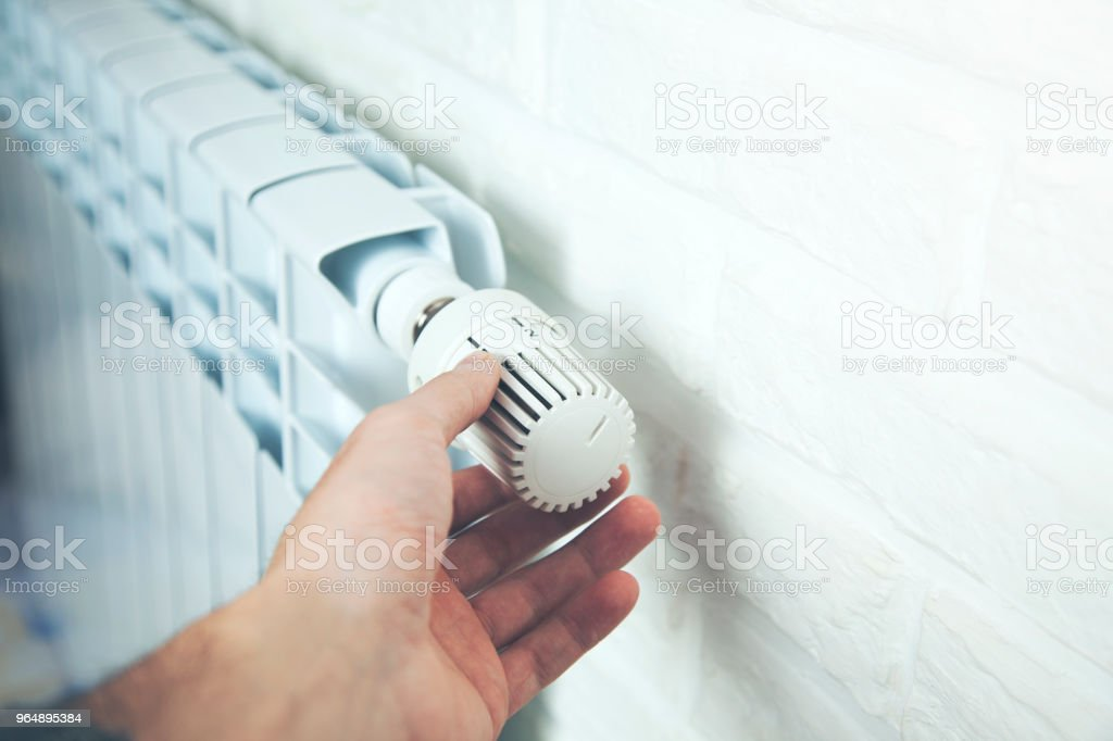 Man Hand Adjusting The Temperature By Thermostat royalty-free stock photo