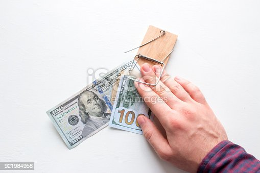 848170878istockphoto man hand caught in a trap with a bribe 921984958