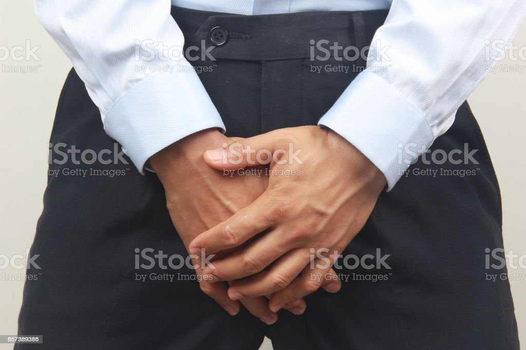 Man hand covering his crotch stock photo