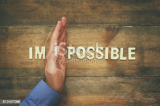istock man hand dividing the letters IM from the word impossible 612407096