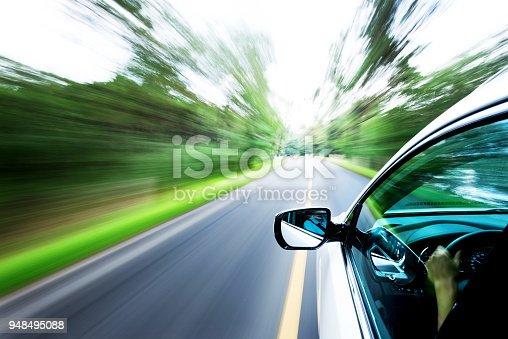 Man hand driving a car through a forest