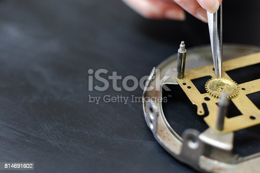 Watchmaker's hand fixes the watch, lots of small parts in the background, black background, close up