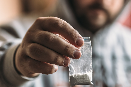 istock Man hand gives plastic packet with cocaine powder or another drugs. Drug dealer selling drugs junkie 862003334