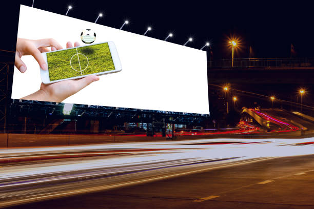 man hand hold and touch screen smart phone or cellphone isolated on billboard with football field on screen stock photo