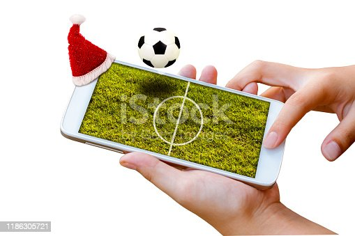 952196272 istock photo man hand hold and touch screen smartphone with Christmas hat and football field on screen. 1186305721