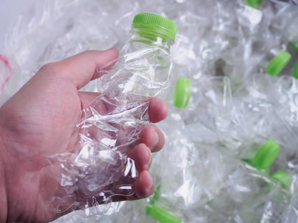 mannen handfattning plastflaskor, återvinning och säker världen från globala uppvärmningen koncept - pet bottles bildbanksfoton och bilder