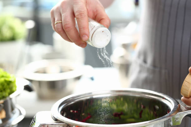 man hand hold saltcellar salt soup cloceup - sodium stock pictures, royalty-free photos & images