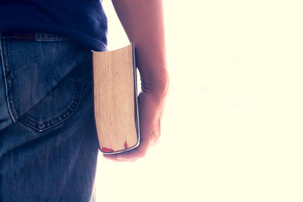 Man hand met een Bijbel geïsoleerd. Vintage kleur. Dit heeft uitknippad. foto