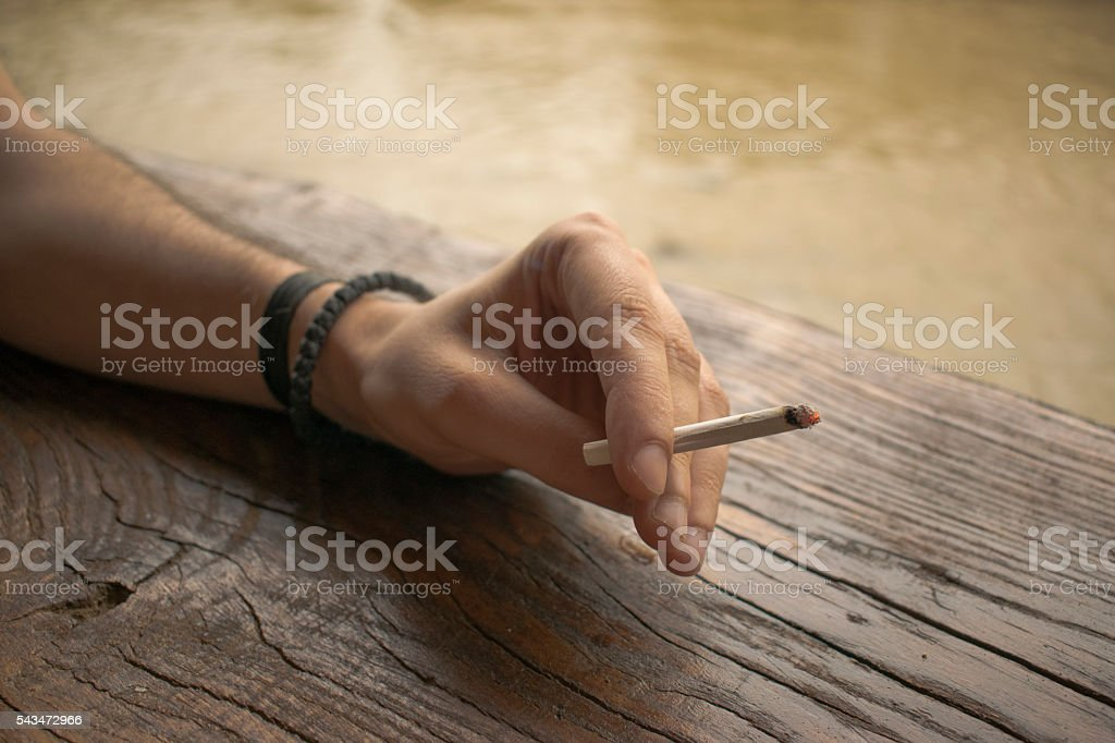 Man hand holding a cigarette with smoke stock photo