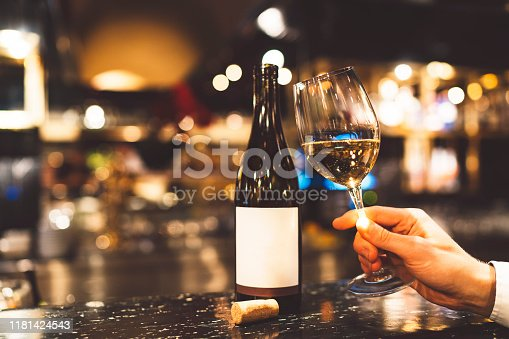 Bottle of red wine on the counter inside a bar. Man hand holding a glass of wine.