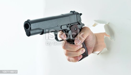 Man hand holding a gun break out of cardboard.